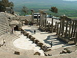 A set of stone seats laid out in a semi-circle to the left overlook a restored stage made up of similar materials to the right. A view of grassy plains precede a wide, mountainous range.