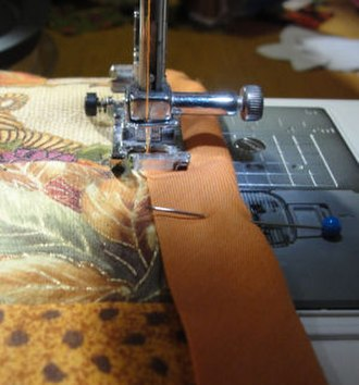 Bias tape - Extra wide double fold bias tape being sewn as a binding on a decorative quilt.