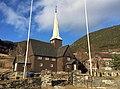 Fåvang Church (kirke) c. 1630, at Tromsnesvegen, Fåvang, Ringebu, Gudbrandsdalen, Oppland, Norway. Graveyard (kirkegård), gate, springtime, stone fence, farms, etc. 2017-04-05 4083.jpg
