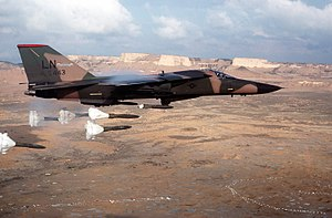 F-111F aircraft releasing its load of Mark 82 high-drag bombs over the Bardenas Reales range.