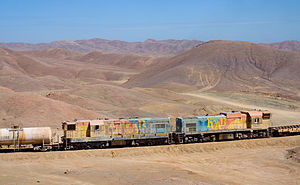 Distributed power - Ferrocarril de Antofagasta a Bolivia EMD GR12U no. 1403 (left) and Clyde G22 no. 1435 (right), marshalled as Distributed Power units, in a long train of loaded sulfuric acid tank cars and empty flat cars on Cumbre pass, Chile, April 2012.