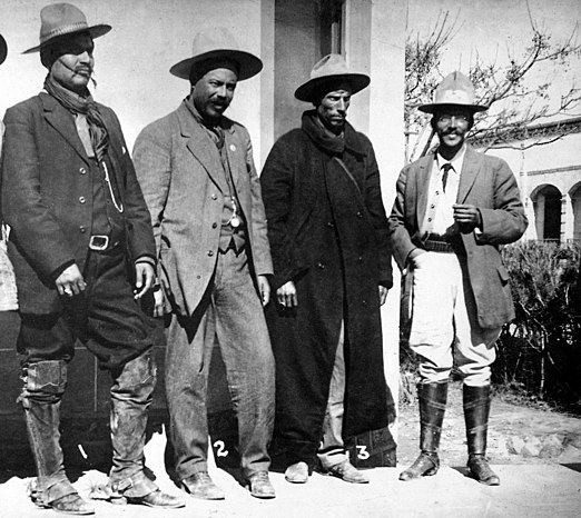 "Northern Revolutionary Gen. Francisco ""Pancho"" Villa with his staff in 1913. Villa is in gray suit in center. His aide, Gen. Rodolfo Fierro, is to Villa's right. To Villa's left is Gen. Toribio Ortega and far right of photo is Colonel Juan Medina. Villa and Fierro served in the Constitutionalist Army opposing Huerta. Once Huerta was ousted in July 1914, Villa joined with Emiliano Zapata in the Army of the Convention and fought his former leader Venustiano Carranza and General Alvaro Obregon. Fierro Pancho Villa Ortega Medina (cropped).jpg"