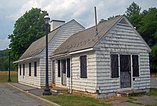 A small white building sided in shingles with a black asphalt bell-shaped roof, seen from its left. A slightly lower eing with a pointed roof projects toward the right. Its doors are screened and locked, and it looks neglected. Two black iron lamppots rise next to a curb and pavement at its left
