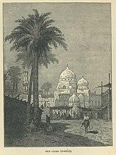 Um homem em um jumento passa por uma palmeira, com uma mesquita e de mercado, atrás Mohamed Kamal