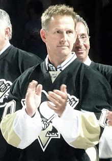 Upper body of a man with short, brown hair applauds. He is wearing a black hockey sweater with white and yellow trim with a stylized penguin logo.