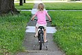 Girl on bike training wheels.jpg
