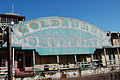 "A faded blue, pink, and gold sign sits on the side of a rusting showboat and displays the words, ""GOLDENROD / NATIONAL LANDMARK / SHOWBOAT / St. Charles, Missouri""."