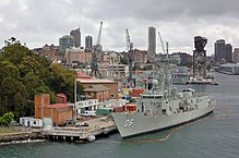 Colour photo of two grey-painted warships moored alongside wharfs. A large crane and several buildings are visible behind the ships.