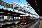 Hankyu 6000 series 60001 set with Osaka Monorail at Hotarugaike Station 2016-10-17.jpg