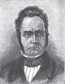 A man with curly, black hair and sideburns wearing a black jacket and white shirt