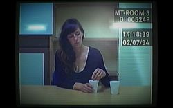 Old computer footage of a 37-year-old woman with long brown hair in a red jacket, sitting at a police interview desk. She is holding her hands together in front of her, and is looking to the right of the camera.
