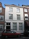 foto van Huis onder met rode pannen belegd schilddak en met gebosseerd gepleisterde lijstgevel, waterlijst boven de onderpui, zesdelige schuiframen