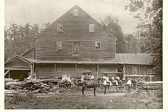 Hooks Mills, West Virginia - Hooks Mill, West Virginia, 1903 -- Saw and lumber mill, waterpower on left; grain was ground on imported stones from France; the post office was on the right. Flour ground from wheat at the mill was stored on the second floor, hay stored on the third floor. Henson Hook, the mill owner, can be seen dressed in white shirt with hand on front wheel of wagon.