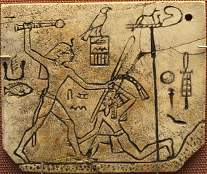 "Wepwawet - Ivory label depicting the pharaoh Den, found at his tomb in Abydos, circa 3000 BC. Originally attached to a pair of royal sandals, which is depicted on the reverse. The side shown here depicts the pharaoh striking down an Asiatic tribesman along with the inscription ""The first occasion of smiting the East."" Wepwawet is at the upper right."