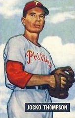 """A middle-aged man in a white pinstriped baseball uniform looks into the camera while facing to the left side. He is wearing a baseball cap with a white """"P"""" on the front, and his jersey reads """"Phillies"""" across the chest."""