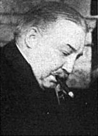 A black-and-white photograph of a balding man with his head bowed smoking a cigar, from the side