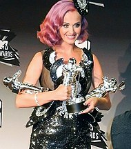 A woman with wavy, shoulder-length pink hair and a black pillbox hat and dress holds three metallic statues.