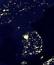 A satellite photo of the Korean Peninsula at night. The largest northern group of lights, Pyongyang is dwarfed by the massive southern group showing Seoul, illustrating large differences in outdoor illumination between North Korea and its neighbours.