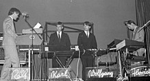 A black and white photograph of four members of Kraftwerk onstage, each with a synthesizer