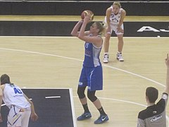 A basketball player lines up a penalty throw. She is wearing a blue top and baggy shorts.