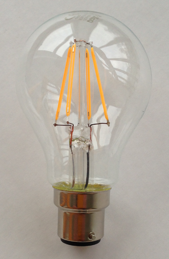 LED filament - A 230-volt LED filament light bulb, with a B22 base. The filaments are visible as the four yellow vertical lines.