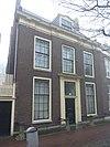 foto van Pand met brede bakstenen gevel, console kroonlijst, vooruitspringende middenpartij, eenvoudige voordeur. Hardstenen stoeppalen