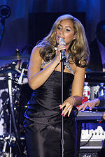 A tanned young woman with dark, highlighted hair wearing a black gown sings into a microphone.