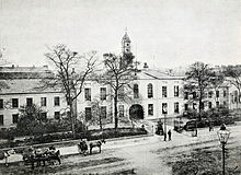 A black and white photograph, showing a stately-looking two storey building with white walls, extending out of shot to the left and right, with an arched cart entrance at the centre. A modest clocktower rises above the entrance, and the building is surrounded by neat shrubbery and iron railings. A wide street crosses left-right outside of the fence, with a handful of horse-drawn carts and pedestrians in 19th century clothing.