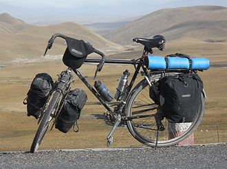 Touring bicycle equipped with front and rear racks, fenders (called mud-guards), water bottles in cages, four panniers and a handlebar bag Loaded touring bicycle.JPG