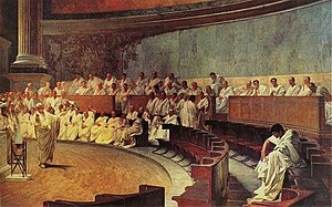 Roman Senate - Representation of a sitting of the Roman senate: Cicero attacks Catiline, from a 19th-century fresco in Palazzo Madama, Rome, house of the Italian Senate. It is worth noting that idealistic medieval and subsequent artistic depictions of the Senate in session are almost uniformly inaccurate. Illustrations commonly show the senators arranged in a semicircle around an open space where orators were deemed to stand; in reality the structure of the existing Curia Julia building, which dates in its current form from the Emperor Diocletian, shows that the senators sat in straight and parallel lines on either side of the interior of the building. In current media depictions in film this is shown correctly in The Fall of the Roman Empire, and incorrectly in, for example, Spartacus.