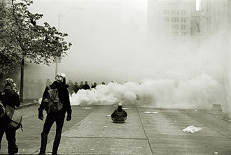"""Insurrectionary anarchism - Protester facing riot police in the """"Battle of Seattle"""""""