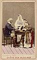 Man och två kvinnor i folkdräkter från Skåne och Blekinge sitter vid bord. Världsutställningen i Paris 1867 - Nordiska Museet - NMA.0039848.jpg