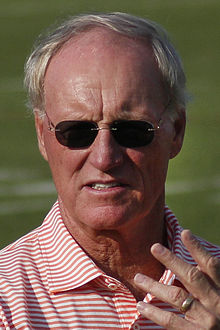 Unposed head and shoulders photograph of Schottenheimer wearing a red and white striped polo shirt and dark sunglasses