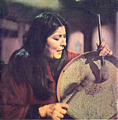 A woman with long black hair playing the percussions.
