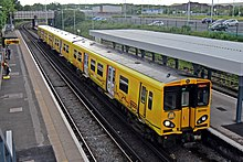 A yellow class 507 train at Birkenhead North station.