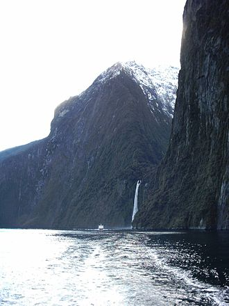 Milford Sound - Cliffs and waterfalls after dry spell, with a two-storey tour boat providing relative size