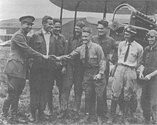A monochrome photograph of eight variously dressed military airmen standing smiling in front of a biplane, with a tall brigadier general in uniform shaking hands with a short-statured, hatless man wearing a long-sleeved shirt and a tie