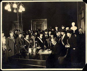 A man sits at a desk sigining a document while a large group of women watches