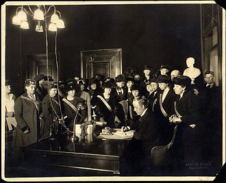 Edwin P. Morrow - Morrow signs the bill ratifying the 19th Amendment, Kentucky Equal Rights Association members look on in celebration, January 6, 1920.