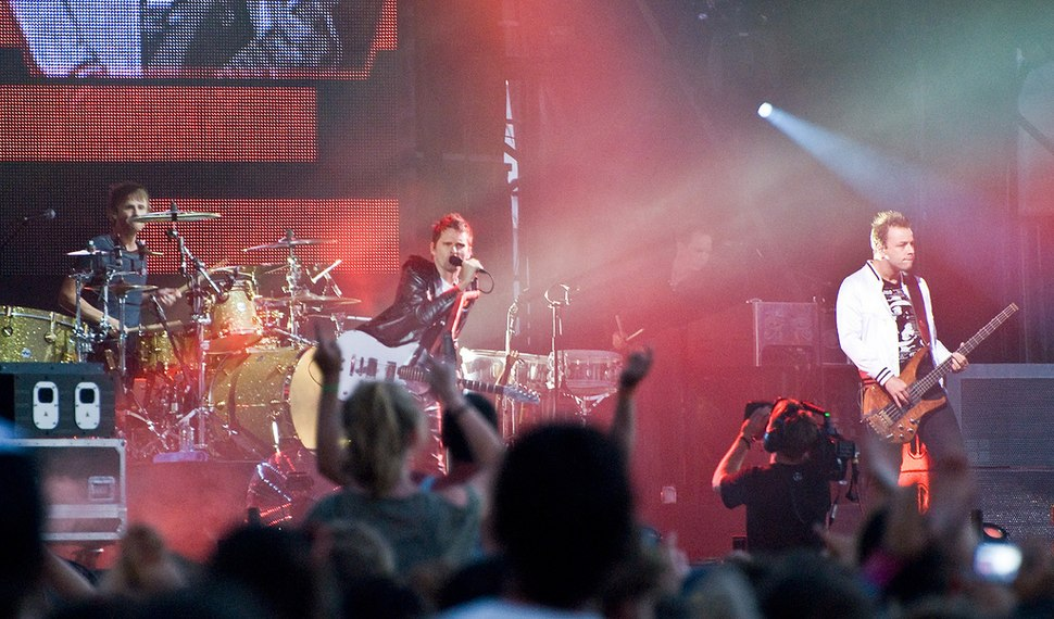 Three men performing on a stage to a crowd of people.
