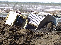 Heavy equipment breaking through thawing muskeg in Wabasca Oil Field in Alberta.