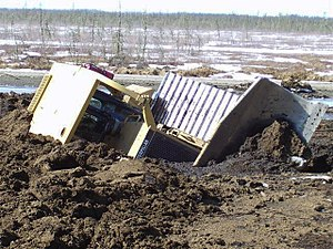 Muskeg - Heavy equipment breaking through thawing muskeg in Wabasca oil field, Alberta.