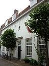 foto van Huis met gepleisterde lijstgevel. In wezen 17e-eeuws huis. Voordeur met houten pilasters