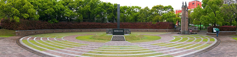 A rectangular column rises above a dark stone base with Japanese writing on it. It sits atop a grass mound with is surrounded by alternating circles of stone path and grass. The is a wall around the whole monument, and bushes beyond.