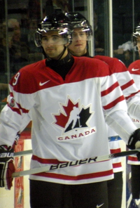 Hockey player in red and white Canada uniform. He has a half-smile on his face and holds his stick in his hands.
