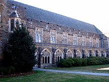 Un exterior de estilo gótico muestra ventanas de catedral con intrincada estructura y piedra oscura, colorido, con arbustos y hierba en el primer plano