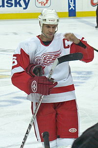 A Caucasian hockey player shown from the knees up. He is wearing a white helmet and a red and white jersey with a winged wheel as a logo