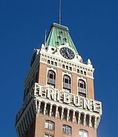 "A clock tower on top of a brown building with the word ""TRIBUNE"" written across it."