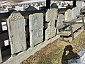 Old tombstones on display at the graveyard (kirkegård) by Sør-Fron Church (Gudbrandsdalsdomen kirke 1792) Hundorp Gubrandsdalen Norway 2017-03-23 Spring sun IMG 1959.jpg