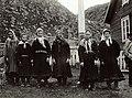 Piker-kvinner (6) i samisk drakt stående på rekke foran flaggstang og inngjerdet hageområde med hus (butikk?) t - Norsk folkemuseum - NF.13322-017.jpg